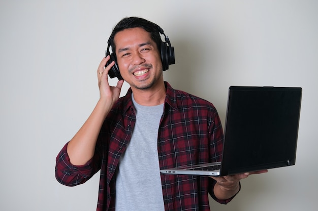 Young asian man smiling happy while wearing headset and holding laptop computer