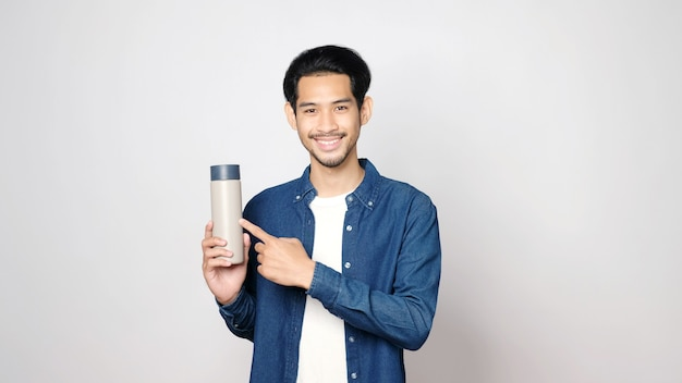 Young asian man smiling and holding reusable bottle looking at camera while standing on isolated gray background
