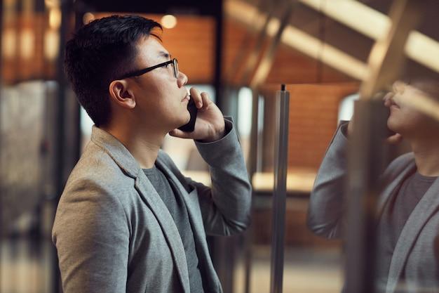 Молодой азиатский мужчина говорит по смартфону