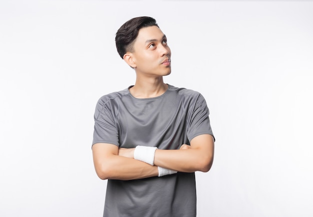 Young asian man in sport outfits arms crossed and looking to copyspace isolated on white wall