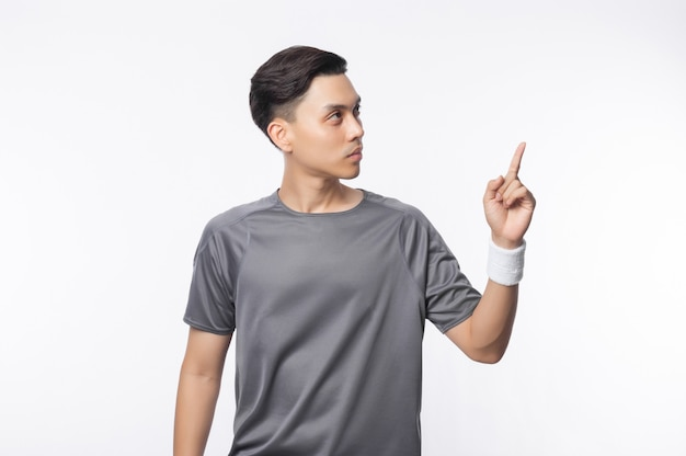Young asian man in sport outfits arms crossed and pointing to copyspace isolated