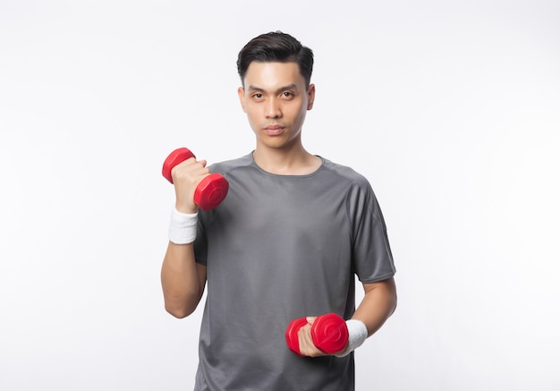 Young asian man in sport outfits exercising with dumbbells and looking to camera isolated on white wall