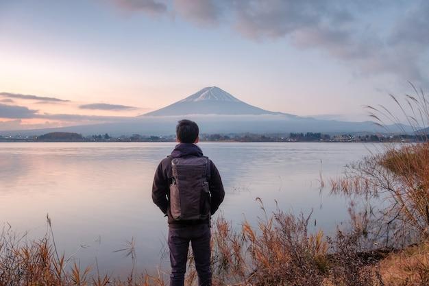 Молодой азиатский мужчина стоит, глядя на гору фудзи на озере кавагутико утром