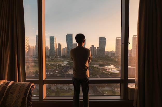 Молодой азиатский мужчина стоит и смотрит в окно в отеле