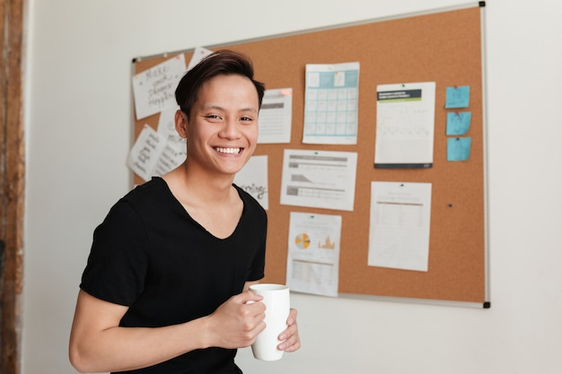 Young asian man standing indoors drinking tea.