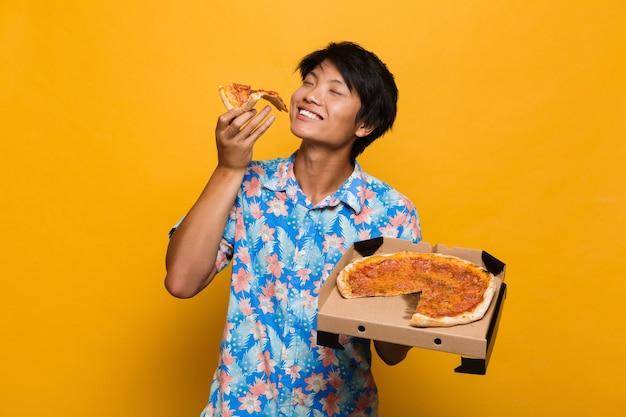 黄色い空間に孤立して立っている若いアジア人男性がピザを食べます。