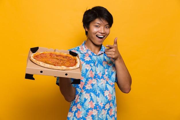 ピザポインティングを保持している黄色のスペースの上に孤立して立っている若いアジア人男性。