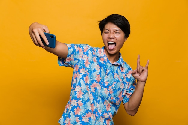 Young asian man standing isolated over yellow space take a selfie by mobile phone showing rock gesture.