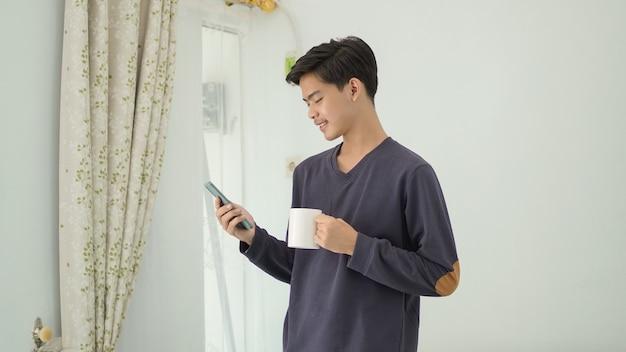 飲み物を持ってスマートフォンを再生して立っている若いアジア人男性