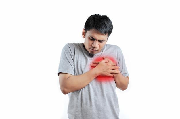 若いアジア人男性は、白い背景で隔離の心臓病や心臓発作に苦しんでいます