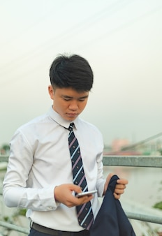 Young asian man in a suit sending message on his hone