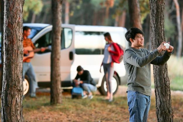 Молодой азиатский человек, делающий фото в лесу