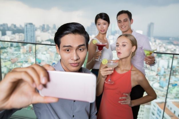 Young asian man taking selfie photo with friends