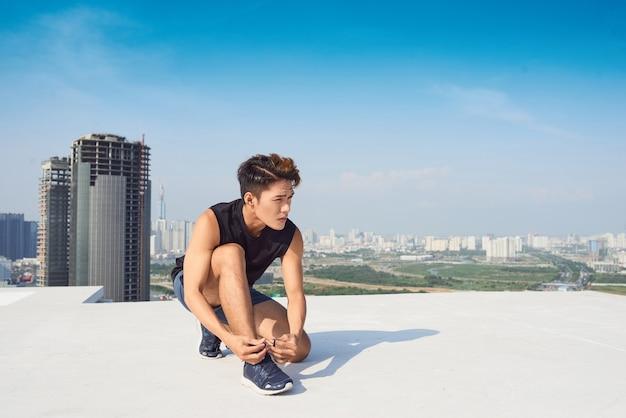 젊은 아시아 남자는 야외에서 달리기 전에 스포츠 신발 끈을 묶습니다.