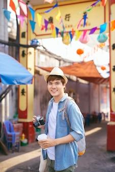 ストリートマーケットを歩いて買い物をする若いアジア人男性旅行者