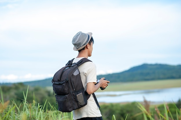Young asian man traveler wearing knitted hat with backpack looking away at amazing lake.