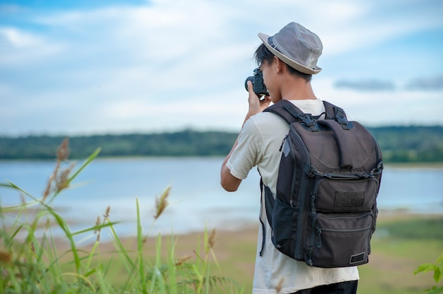 Young asian man traveler wearing knitted hat with backpack taking a photo and looking at amazing lake.