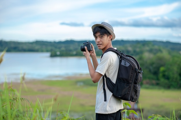 Young asian man traveler with backpack digital camera look at the camera with beautiful nature lake background. Premium Photo