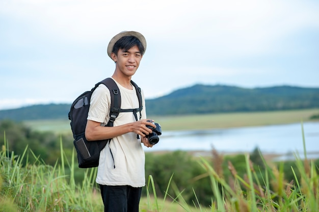 Young asian man traveler with backpack digital camera look at the camera with beautiful nature lake background.