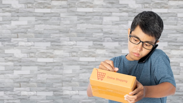 Молодой азиатский человек используя smartphone принимая проверяющ онлайн заказ покупок покупки.