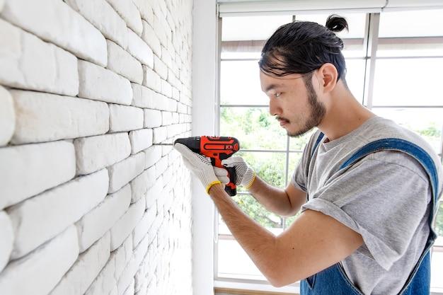 방의 흰색 벽돌 벽에 전기 드릴을 사용하는 젊은 아시아 남자, 가정 개선을 위한 개념.