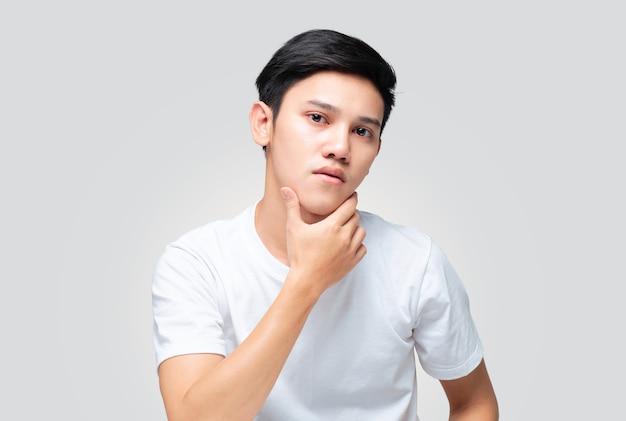 손을 사용하는 젊은 아시아 사람이 자신의 피부를 확인하기 위해 턱을 만집니다.