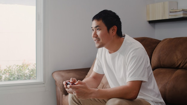 Young asian man using joystick playing video games in television in living room, male feeling happy using relax time lying on sofa at home. men play games relax at home .
