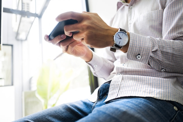 Young asian man using  mobile device smart phone at a workplace - technology concept