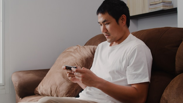 Young asian man using mobile phone playing video games in television in living room, male feeling happy using relax time lying on sofa at home. men play games relax at home .