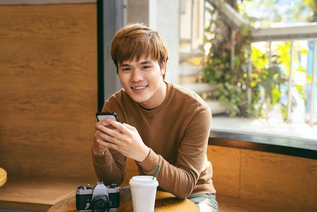 朝食、コーヒータイム、夏休みの概念を持っている間にスマートフォンを使用して若いアジア人