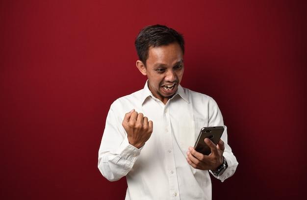 스마트폰을 사용하여 서 있고 자랑스럽게 비명을 지르며 승리를 축하하는 젊은 아시아 남자