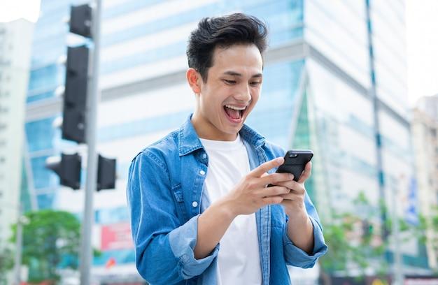通りを歩きながらスマートフォンを使用して若いアジア人男性