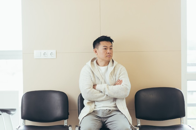 Young asian man waiting for an interview or meeting sitting in the hallway in the waiting room. student or entrant in the reception for exam or employment hr. male patient in office a hospital clinic