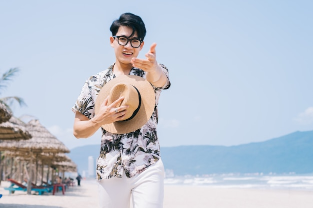 Young asian man walking on the beach