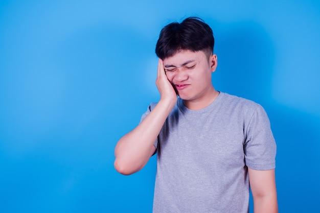 若いアジア人男性は、青い背景に敏感な歯や歯痛のある灰色のtシャツを着ています。ヘルスケアの概念。
