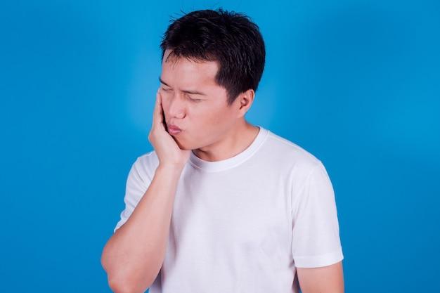 若いアジア人男性は、青い背景に敏感な歯や歯痛のある白いtシャツを着ています。ヘルスケアの概念。