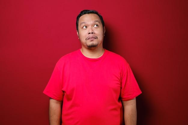 若いアジア人男性は、赤い背景の上に思考と見ているアイデアのジェスチャーで赤いシャツを着ています