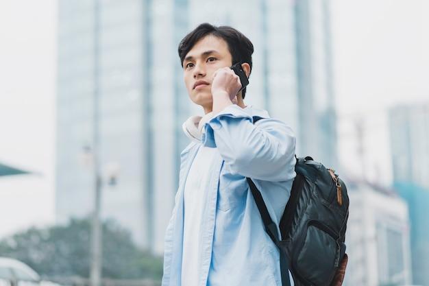 バックパックを身に着けている若いアジア人男性と電話中