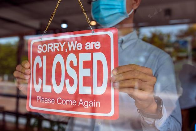 의료 마스크를 착용하고 자신의 가게를 닫으려면 기호를 들고 젊은 아시아 남자.