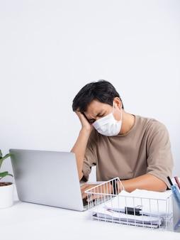 보호 마스크를 쓰고 젊은 아시아 남자는 사무실에서 기분이 나쁘고 일하면서 스트레스가 많은 두통이 있습니다. 스튜디오 촬영에 고립 된 흰색 배경.