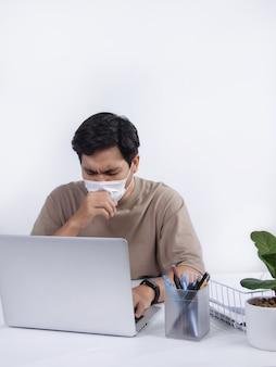 保護マスクを着用した若いアジア人男性は、オフィスで気分が悪く、発熱と咳の症状があります。白い背景で隔離のスタジオショット。