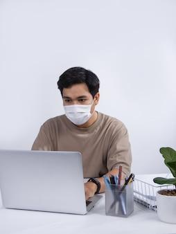 Молодой азиатский человек в защитной маске, рабочий проект на своем портативном компьютере в офисе. студия выстрел, изолированные на белом фоне.