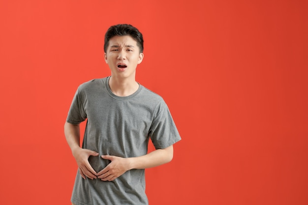 Молодой азиатский мужчина в белой футболке болен, страдает от боли в животе