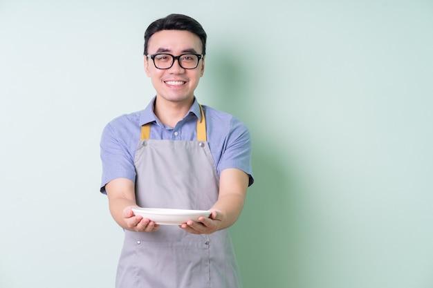 緑の背景にポーズをとってエプロンを身に着けている若いアジア人男性