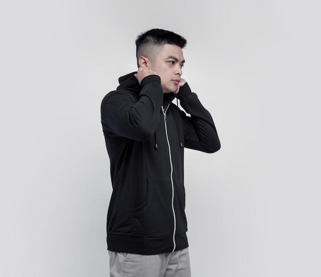 Молодой азиатский мужчина в черной толстовке с капюшоном на молнии, изолированной на стене