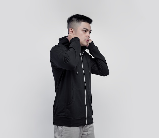 Young asian man wearing black hoodie zipper isolated on wall