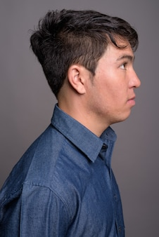 Young asian man wearing blue shirt against gray wall