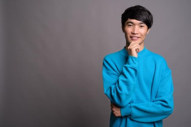 Молодой азиатский мужчина в синем свитере на серой стене