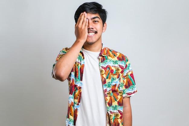 片目を手で覆うカジュアルなカジュアルなビーチシャツを着て、白い背景の上に、自信を持って笑顔と驚きの感情を身に着けている若いアジア人男性。