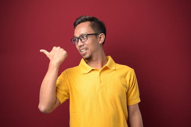 カジュアルな服と眼鏡をかけて親指を横に向けて幸せそうに笑っている若いアジア人男性